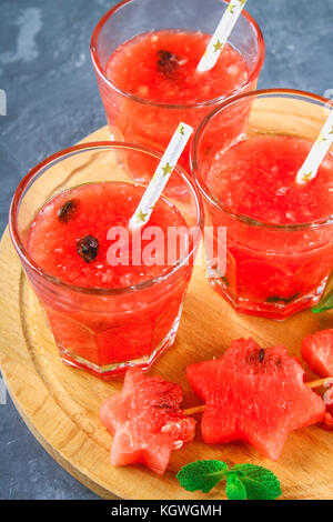 Watermelon smoothies in glasses with mint leaves on a gray dark concrete background - Stock Photo
