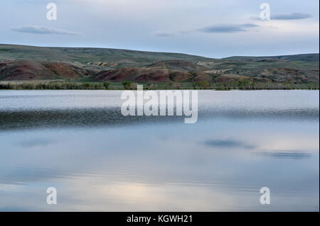 Beautiful summer landscape with a lake and colored mountains on the background of an overcast sky and clouds in - Stock Photo