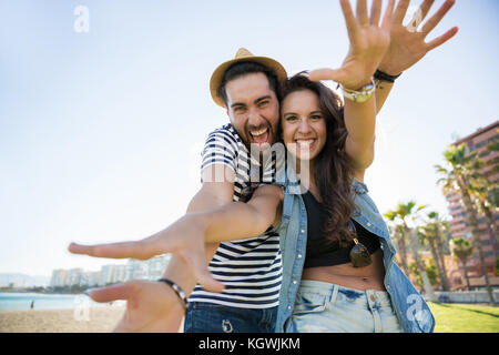 Portrait of happy couple raising hands in front of them laughing - Stock Photo