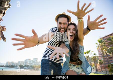 Portrait of happy couple raising hands having fun - Stock Photo