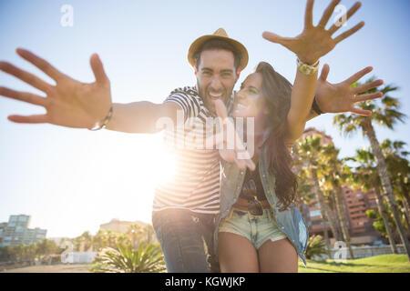 Portrait of happy couple raising hands in sunlight having fun - Stock Photo
