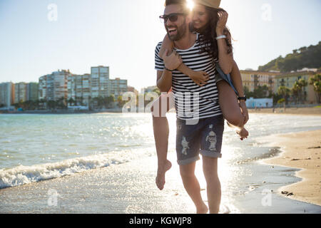 Portrait of happy man giving his girlfriend a piggyback laughing - Stock Photo