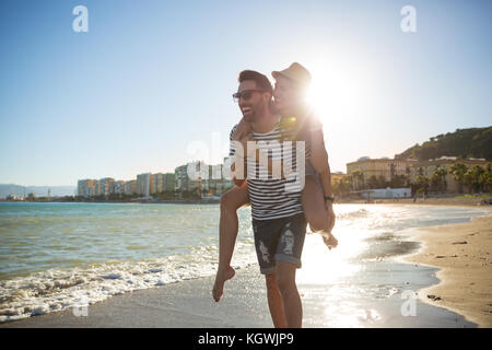 Portrait of happy man giving his girlfriend a piggyback in sunlight on beach - Stock Photo
