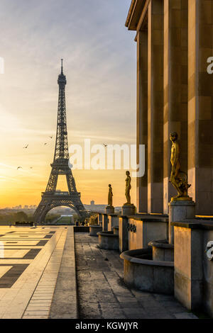 The rising sun illuminates the Trocadero esplanade and its golden statues while the Eiffel Tower stands out against - Stock Photo