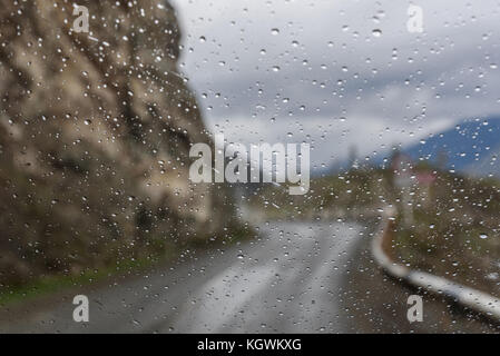 View of the bend asphalt road on a mountain pass through window glass of the car covered by rain drops - Stock Photo