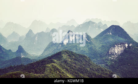 Retro toned picture of karst formations landscape around Guilin on a foggy day. It is one of China most popular - Stock Photo