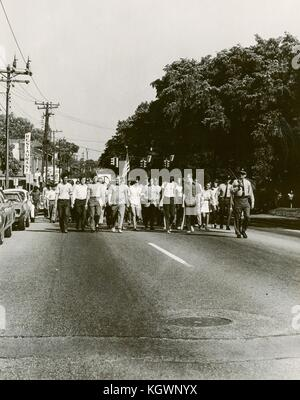 A group of student protests, escorted by a Sheriff's deputy, marches down a street carrying American flags and hippie - Stock Photo