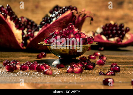 Pomegranate slices and seeds of pomegranate fruits on the vintage table Stock Photo