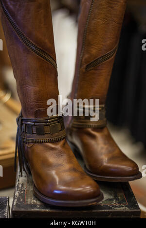 Pair of women's brown leather boots designed in western style displayed on a vintage shoe box - Stock Photo