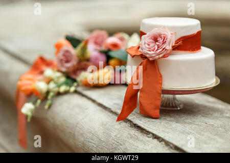 white wedding cake with red flower - Stock Photo