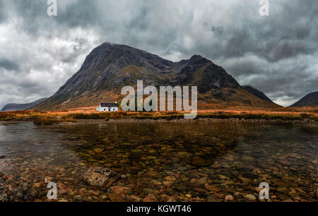 Traditional white stone house in Glencoe Valley with a mountain in the background and a river in the foreground. - Stock Photo