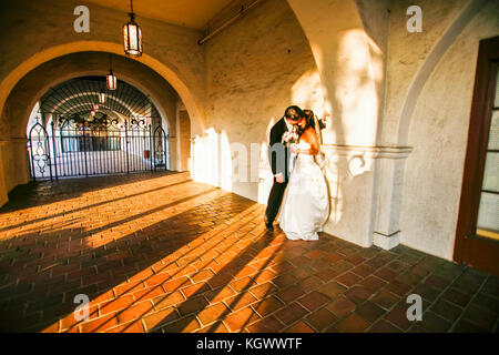 A groom is kissing a bride in an arch hallway with light streaking and shadows - Stock Photo