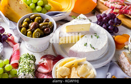 Charcuterie assortment, cheeses, olives and fruits   on a white wooden background. - Stock Photo