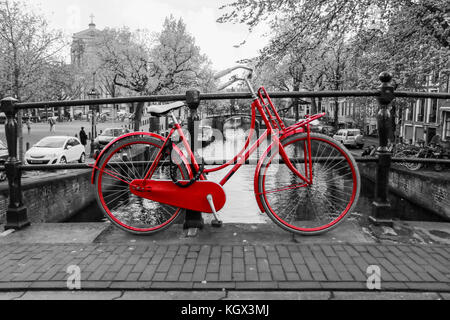 A picture of a lonely red bike on the bridge over the channel in Amsterdam. The background is black and white. - Stock Photo