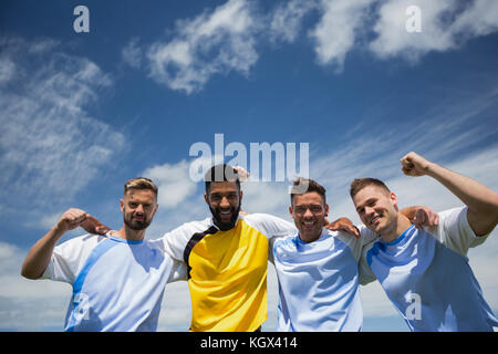 Portrait of excited football players standing together with arm around - Stock Photo