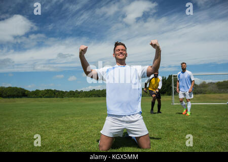 Excited football player in celebrating scoring goal kneeling on grass pitch on a sunny day - Stock Photo