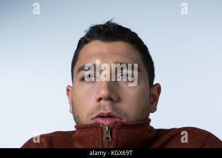 Close-up of scared man standing against white background - Stock Photo