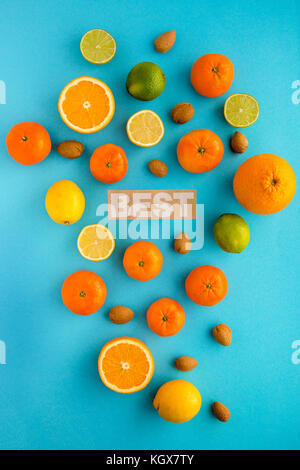 Photo of citrus fruits, lemons, oranges, limes, mandarines, nuts, view from above, cyan background, isolated - Stock Photo