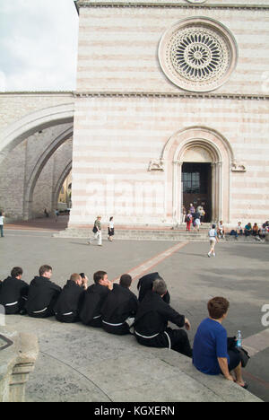 Group of priests relaxing in front of Assisi main church. Umbria, Italy - Stock Photo