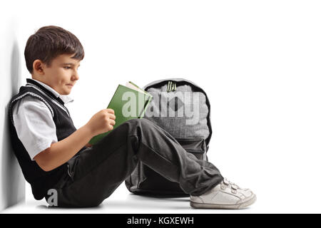 Little schoolboy seated on the floor reading a book and leaning against a wall isolated on white background - Stock Photo
