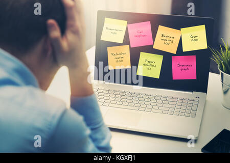 busy businessman under stress due to excessive work in office - Stock Photo