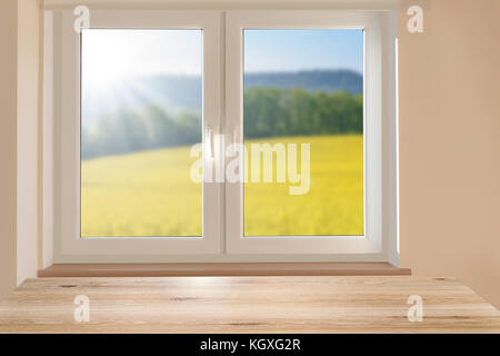 Composite image - mockup of an empty table on a background of a beautiful sunny mountain landscape in a room window. - Stock Photo