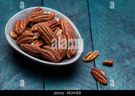 Pecans on petrol-colored wood in shell. - Stock Photo