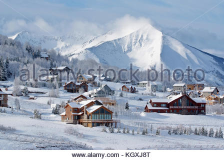 Early morning sun lights homes in Mount Crested Butte, Colorado with Whetstone Mountain in the distance. - Stock Photo