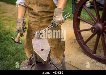 Blacksmith working on an iron object with a hammer during a workshop. - Stock Photo