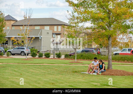 Man and woman, young couple, relaxing, sitting in a public park for lunch in Montgomery, Alabama USA. - Stock Photo