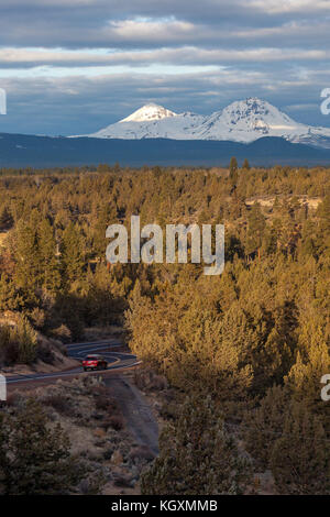 A red car drives along a curvy road with the mountains of the Three Sisters Wilderness during sunset in Bend, Oregon. - Stock Photo