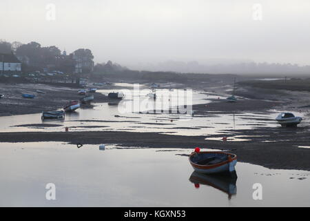 Low tide on River Burn, Norfolk. Evening mist over Burnham Overy Staithe. Boats dried out on mud flats. Wildfowl - Stock Photo