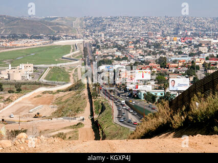 US-Mexico international border between Tijuana, Mexico (right) and San Diego, California (left) separated by a corrugated - Stock Photo