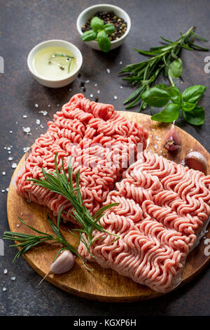 Assorted minced pork and beef with fresh leaves of rosemary and basil. Copy space. - Stock Photo