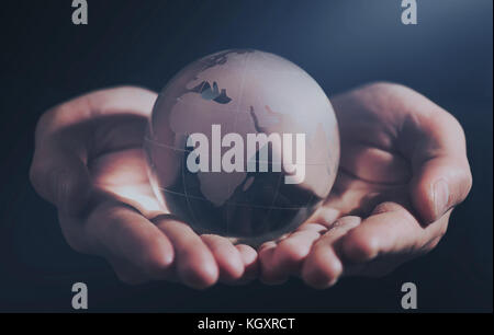 Business man holding Earth planet in palm - Stock Photo