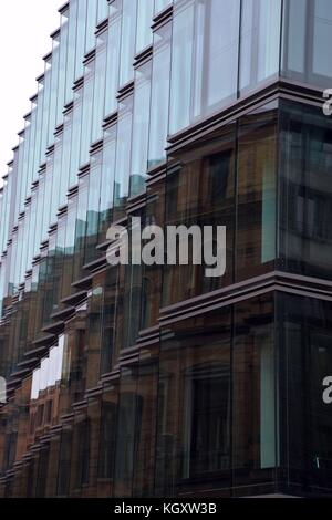 Abstract old house made of bricks reflected in a new and modern glass facade - Stock Photo