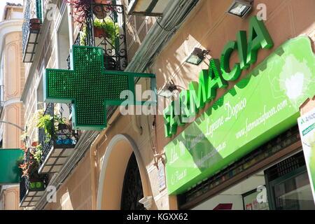 Green sign neon cross Farmacia pharmacy shop, Madrid city centre, Spain - Stock Photo