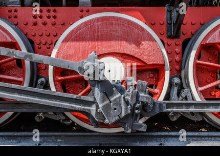 Red frame and wheels of a steam locomotive with cranks, rods and axles. - Stock Photo