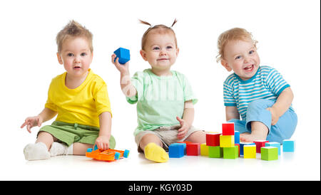 Funny children group playing colorful toys isolated on white - Stock Photo