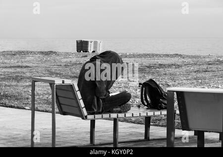 A teenager in a large hood sits on a bench by the sea and reads a book. Black and white photo. - Stock Photo