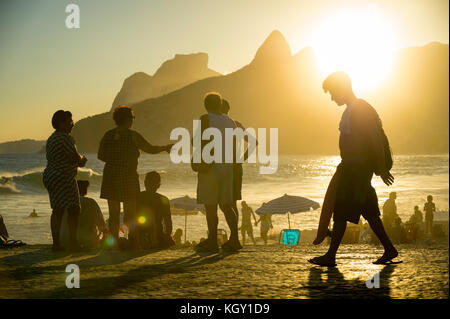 RIO DE JANEIRO - MARCH 20, 2017: People gathered watching the sunset at Arpoador, a popular summertime activity - Stock Photo