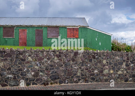 Corrugated iron shed, tin hut, derelict, boarded up in Laytown, County Meath, Ireland