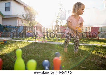 Cute toddler girl playing with bowling toy in grass in sunny backyard - Stock Photo