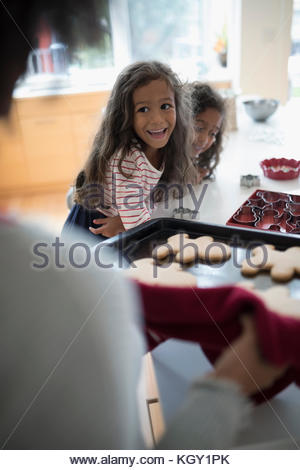 Excited daughters watching mother with fresh, hot Christmas gingerbread cookies - Stock Photo