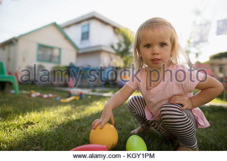 Portrait curious blonde toddler girl playing with toys in backyard - Stock Photo