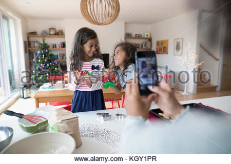 Mother with camera phone photographing daughters decorating Christmas gingerbread cookies in kitchen - Stock Photo