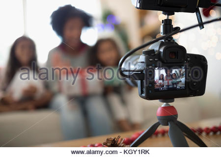 View through camera viewfinder of mother and daughters opening Christmas gifts - Stock Photo