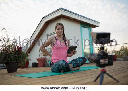Female yoga instructor with digital tablet and video camera filming, vlogging on yoga mat on deck patio - Stock Photo