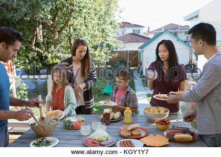 Neighbor families enjoying barbecue on patio - Stock Photo