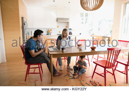 Parents working at laptops at table with children playing - Stock Photo